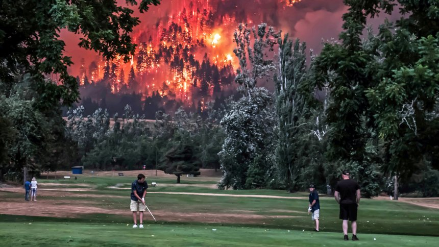 The Eagle Creek wildfire burns as golfers play at the Beacon Rock Golf Course in North Bonneville, Washington, U.S. September 4, 2017. Picture taken on September 4, 2017. REUTERS/Kristi McCluer TPX IMAGES OF THE DAY - RC1E359FB9F0